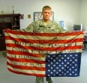 soldier w upsidedown US flag w writing: 'No flag large enough...'